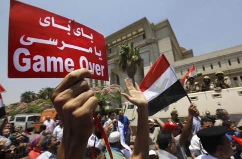 """Egyptian revolutionaries during the 30th of June revolution, 2013 holding up banners calling to depose the 1-year islamist president Morsi. Banner reads: """"Bye bye Morsi ... Game over!"""" as an indication of rejection of radical Islamism and extremist political islamists in Egypt."""