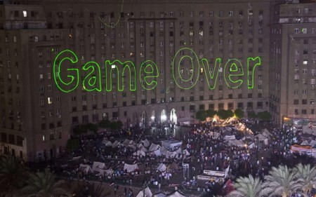 "Egyptians declaring the start of the end of all radical Islamism during their 30th of June revolution. Protesters show a large ""Game over"" sign on the Tahrir square building in Cairo, Egypt 30-6-2013."