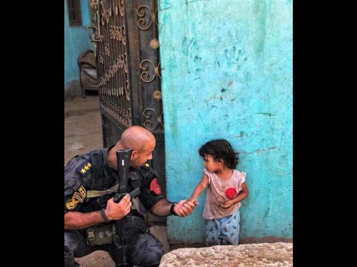 2018-09-22 Egyptian Police officer Ahmed Nafae with young girl during police operations in Cairo - Masrawy