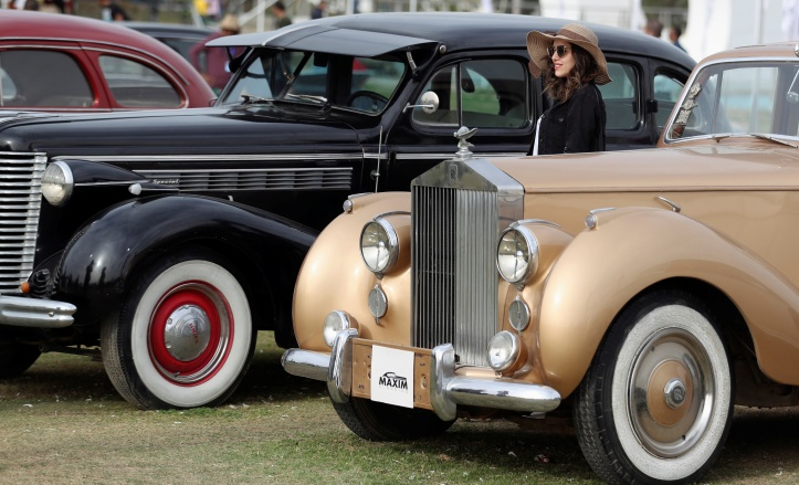 A woman stands next to a black classic Buick Special model and a golden Rolls-Royce Silver Dawn model at the 7th Cairo Classic Meet in Cairo